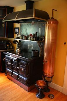 The kitchen has a steampunk/19th century design with an elaborately decorated cast-iron wood-burning stove and electric cooktop.